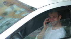 Man talking on a cell phone while sitting in the car. smiling driver Stock Footage