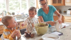 A woman making a cake with cute boys in the kitchen dolly shot Stock Footage
