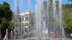 City park with a fountain. One can see the theater building, trees and people Stock Footage