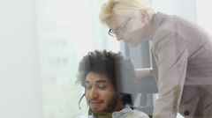 Senior member of staff working with middle eastern man in call centre office wit Stock Footage