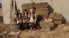 Three Women in the National Ukrainian Costume Sitting on Straw Bales in the Stock Footage