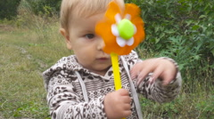 Baby boy playing  with a toy in his hand  in autumn  day in park outdoors. Stock Footage