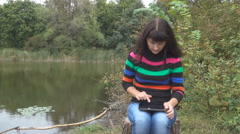 Beautiful young  woman using tablet pc at autumn park. Pretty young woman in Arkistovideo