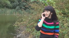 Beautiful young  woman talking on smart phone at autumn park. Pretty young wo Stock Footage