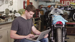 Man using laptop near motorcycle Stock Footage