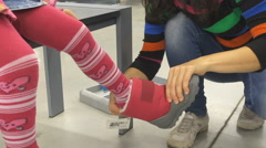 A little baby girl and his mother are choosing warm winter rubber boots in th Stock Footage