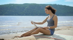 A beautiful sexy young lady is sitting at a beach using laptop Stock Footage