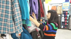 Woman Shopping for Clothing. Young women carefully picking up clothes. Pretty Stock Footage