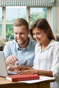Male Home Tutor Helping Teenage Girl With Studies Stock Photos