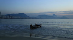 Fishermen push their boat out to sea in Brazil at sunset Stock Footage