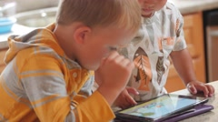 Dolly shot of boys playing with an iPad at home Stock Footage