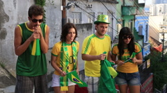 Four Brazilian football fans stand outside and cheer for their team Stock Footage