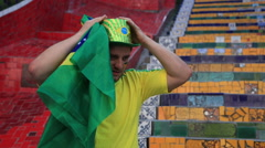 A Brazilian soccer fan celebrates while watching the game Stock Footage