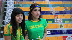 Two female Brazilian soccer fans celebrate while watching the game Stock Footage
