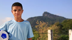 A boy stands in front of a mountain while holding a soccer ball Stock Footage