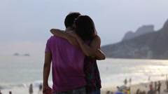 A couple hug and kiss as they stand by the beach and look out at the mountains Stock Footage
