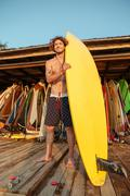 Professional young surfer getting board ready for surf Stock Photos