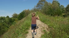 Back view of little boy with a wooden sword runs up the hill, 4k steadicam shot Stock Footage