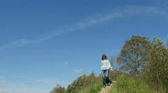 Woman in blue blouse & jeans walks down the footpath in the countryside, 4k shot Stock Footage