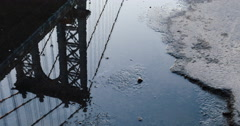 The manhattan Bridge reflected in a puddle - 4k Stock Footage