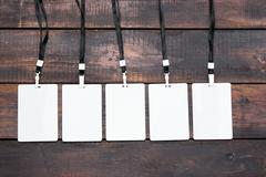 The five card badges with ropes on wooden table Stock Photos