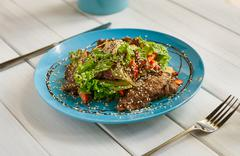 Restaurant food on wooden table. Warm meat salad with sesame Stock Photos