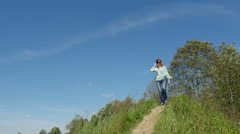 Woman in blue blouse & jeans walks down the footpath in the countryside, Full HD Stock Footage