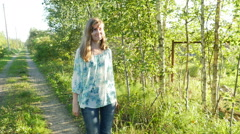 Happy woman in blue blouse & jeans walks on green alley in the countryside Stock Footage