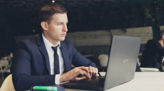 Man in suit sitting in cafe ,laptop on wooden table Stock Footage