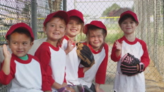 Children waving while playing baseball Stock Footage