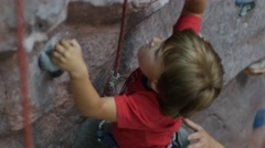 View of little boy in red t-shirt climbing on artificial climbing wall, 4k shot Stock Footage