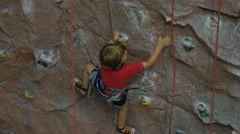 A little boy climbs on the training wall on the climbing gym, 4k shot Stock Footage