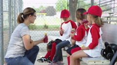 Little league team drinking and eating snacks Stock Footage
