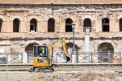 Excavator in front of ancient ruins of Rome, Italy Stock Photos