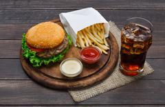 Fast food take away. Hamburger, cola and fries on wood Stock Photos