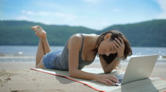 A beautiful sexy joyful smiling lady is laying on her tommy at a beach using Stock Footage