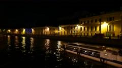 Moyka River at night, tourist boat sail along, old building facade, shaded bank Stock Footage