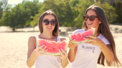 Two pretty girls breaks off a piece of watermelon and eating Stock Footage