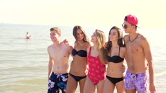 Group of friends hugging while walking at beach and starts to run  Stock Footage