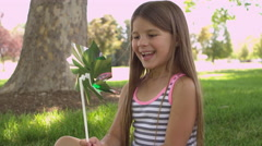 Little girl playing with pinwheel Stock Footage
