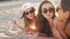 Three beautiful women in sunglasses lies on the beach. Stock Footage