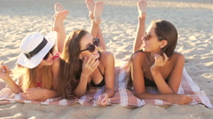 Three beautiful women in sunglasses lies on the beach.  Stock Footage