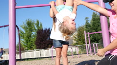 Mom and daughters play on jungle gym Stock Footage