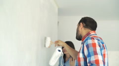 Young couple fighting, arguing while painting wall at their new home Stock Footage