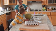 Mother making cake with her little boys in the kitchen dolly shot Stock Footage