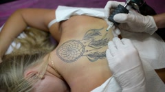 Tattoo Master does Color Tattoo on Female Back Stock Footage