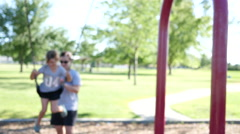 Family playing on swing set Stock Footage