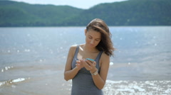 A young beautiful lady booking a hotel while standing at a beach Stock Footage