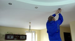 Electrician guy installing or replacing a halogen spot light lamp into ceiling Stock Footage