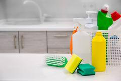 Basket with cleaning items on blurry background place for text, Top view, fla Stock Photos